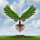 Moving Up. And the power of success with a growing  tree in the shape of wings that has emerged out of the ground and has taken flight upward to opportunity as Royalty Free Stock Image