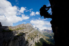 Moving up. Silhouette of a climber above mountain peaks Stock Photography