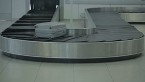 Moving valise on the luggage conveyor in the airport. Close-up. The camera focuses on the luggage belt of the baggage claim desk at the airport. The luggage stock video footage