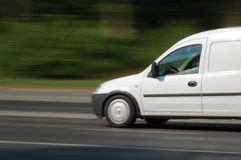 Moving van. White van moving fast at main street royalty free stock image