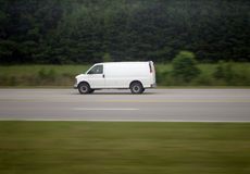 Moving Van. White van speeding down a rural highway Royalty Free Stock Photos