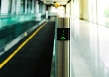 Moving walkway shown signage lighting screen, journey and traveler concept, selective focus. Post of a part of moving walkway shown signage lighting screen stock photography