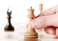 Moving white chess queen on a chessboard Stock Images