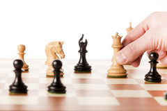Moving white chess queen on a chessboard Royalty Free Stock Photos