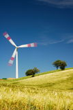 Moving wind turbine in golden meadow Stock Images