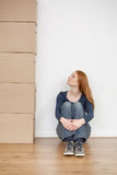 Moving In - Woman with Boxes. A young woman sitting on the floor of an empty room next to a stock of moving boxes Royalty Free Stock Photo