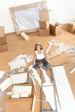 Moving woman in new home. Sitting on floor unpacking and assembling furniture.  Multiracial Asian Caucasian young woman Royalty Free Stock Images
