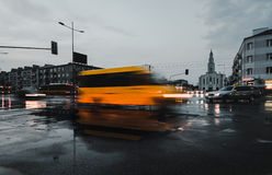 Moving yellow delivery van. A crossroad in Warsaw with moving vehicles after heavy rain stock image