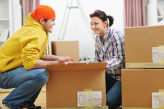 Moving young couple searching something in box. Moving young happy couple searching something in box stock image