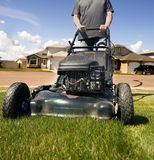 Mow the lawn. Mowing the front lawn with houses in the background Stock Photos