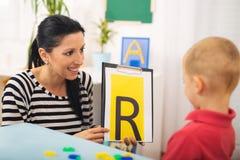 Mowa terapeuta uczy chłopiec mówić list R fotografia stock