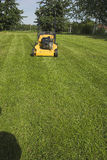 Mowed grass. Picture of the mowed grass with lawnmower in the background Stock Images