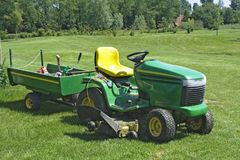 Mower on golf course. Green mini tractor with mower and cart on golf course royalty free stock photography