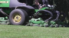 Free Mower Work In The Grass At The Edge Of A Golf Course. Cutting Grass With A Big Machine Stock Photos - 141867483