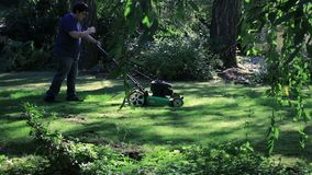 Mowing across yard and then behind a tree. Young man mowing lawn in large green yard stock footage