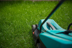 Mowing and cutting the long grass with a lawn mower, closeup. Cutting the lawn machine on the green grass Royalty Free Stock Images