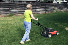 Mowing on electric power. Pushing a battery-powered mower.  Much better for the environment Royalty Free Stock Photo