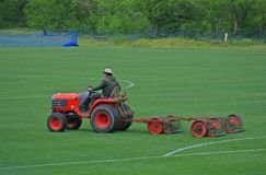 Mowing the Field. Man on tractor aerating a soccer field Royalty Free Stock Images