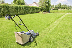 Mowing the gras. Image with a lawn mower ready to cut the gras on a sunny day royalty free stock image