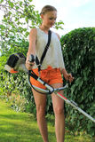 Mowing the Grass. Young woman Mowing the Grass Stock Photo