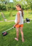 Mowing the Grass. Young woman Mowing the Grass Royalty Free Stock Photo