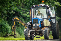 Mowing the grass along the road in the Kaluga region of Russia. Royalty Free Stock Images