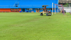 Mowing grass in a football stadium Royalty Free Stock Image