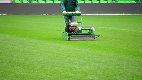 Mowing grass in a football stadium stock video footage