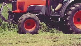 Mowing the grass - worker is driving red   tractor, mowing the grass in the public park. Belgrade, Serbia - July 06, 2019:  Mowing the grass - worker is driving stock video footage