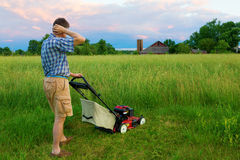 Mowing Job. Man is tasked to mow a field of tall grass Stock Photos