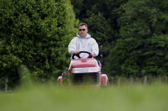 Mowing The Lawn. A man mowing the lawn on a riding mower stock images