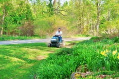 Mowing the lawn. Adult caucasian man on a lawnmower mowing grass lawn in late spring afternoon Royalty Free Stock Images