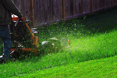 Mowing Lawn. Gardening worker Mowing backyard lawn during sunny day Royalty Free Stock Photo