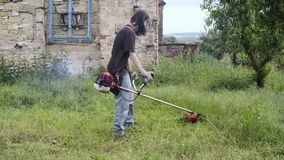 Mowing lawn man brush cutter worker countryside stock video