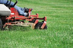Mowing the lawn. Outdoor worker mowing the lawn by lawnmower Stock Photos