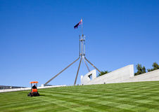Mowing the lawn which covers the roof of Parliament. House in Canberra is a full time job following plentiful rains during the summer months Royalty Free Stock Photography
