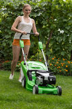 Mowing the lawn. Young woman mowing the lawn Royalty Free Stock Photography