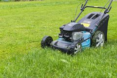 Mowing lawns. Lawn mower on green grass. mower grass equipment. mowing gardener care work tool close up view sunny day. Mowing lawns. Lawn mower on green grass royalty free stock photos