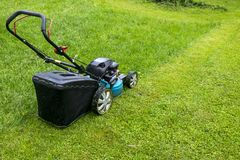 Mowing lawns. Lawn mower on green grass. mower grass equipment. mowing gardener care work tool close up view sunny day. Royalty Free Stock Photo