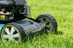 Mowing lawns. Lawn mower on green grass. mower grass equipment. mowing gardener care work tool close up view sunny day. Royalty Free Stock Images