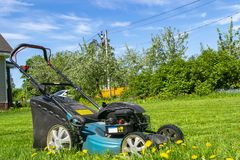 Mowing lawns. Lawn mower on green grass. Mower grass equipment. Mowing gardener care work tool. Close up view. Sunny day. Soft lig. Htning stock images