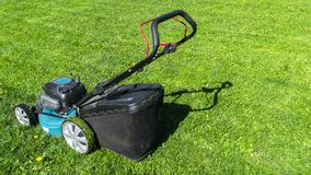 Mowing lawns. Lawn mower on green grass. Mower grass equipment. Mowing gardener care work tool. Close up view. Sunny day. Soft. Mowing lawns, Lawn mower on green royalty free stock photos
