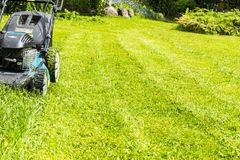 Mowing lawns, Lawn mower on green grass, mower grass equipment, mowing gardener care work tool, close up view, sunny day Stock Photography