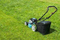 Mowing lawns. Lawn mower on green grass. mower grass equipment. mowing gardener care work tool close up view sunny day. Stock Photography