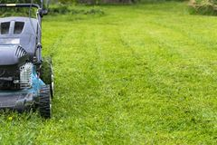 Mowing lawns. Lawn mower on green grass. mower grass equipment. mowing gardener care work tool close up view sunny day. Stock Image