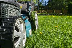 Mowing lawns, Lawn mower on green grass, mower grass equipment, mowing gardener care work tool, close up view, sunny day. Soft lig. Htning royalty free stock photos