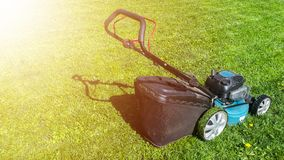 Mowing lawns, Lawn mower on green grass, mower grass equipment, mowing gardener care work tool, close up view, sunny day. Soft lig. Htning stock photography