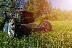 Mowing lawns, Lawn mower on green grass, mower grass equipment, mowing gardener care work tool, close up view, sunny day. Soft lig. Htning royalty free stock image