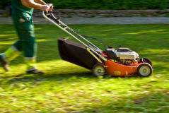 Mowing machine. Gardener with a mowing machine cutting the grass in a park Royalty Free Stock Photography