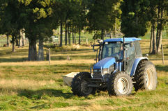 Mowing pasture. Tractor mowing pasture for silage, West Coast, South Island, New Zealand Stock Photography